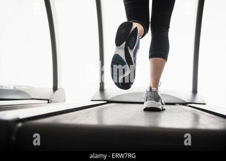 Legs of mixed race woman running on treadmill