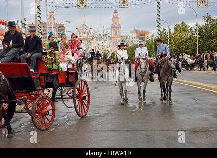 Mule drawn carriages and horseback riders on Antonio Bienvenida street with Main Gate 2015 Seville April Fair Spain - Stock Photo