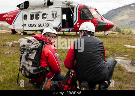 A Welsh Search and Rescue Dog team prepare to board a Bristows S-92 rescue helicopter during a training exercise - Stock Photo