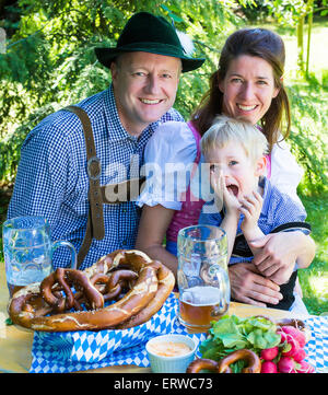 bavarian family sitting outside on a bench and smiling - Stock Photo
