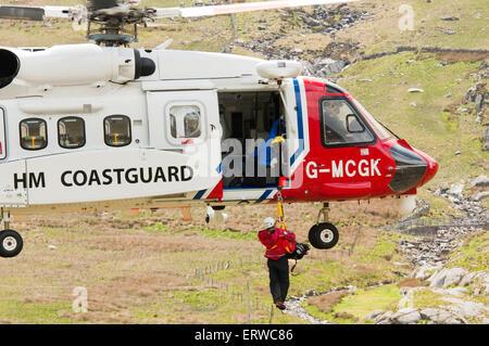 A mountain rescuer is winched into a skillfully hovering Sikorsky S-92 helicopter operated by Bristow for HM Coastguard - Stock Photo