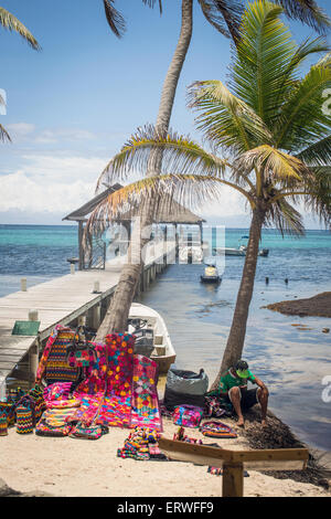 A Belizean vendor selling local arts and crafts to tourists on the beach on the island of Ambergris Caye. - Stock Photo