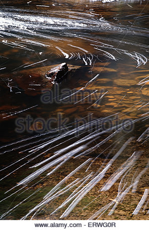 Repentance Creek at Minyon Falls - bubbles causing streaks across the surface in this dramatic long exposure image - Stock Photo