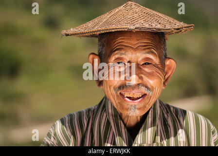 A farmer in rural Bhutan pauses as he tends to his livestock. - Stock Photo