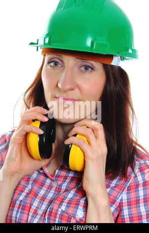 Female construction worker wearing green helmet and protective headphones, safety at work and ear protection. - Stock Photo
