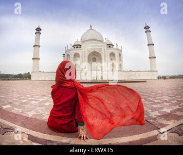 Woman in red costume with flattering scarf sitting near Taj Mahal in Agra, Uttar Pradesh, India - Stock Photo