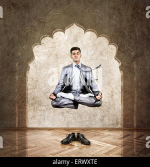 Indian businessman doing meditation in the air in lotus pose at the office with arch on the wall - Stock Photo