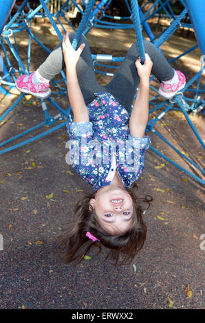 Little child (girl age 05) play on spider web bar in a outdoor playground - Stock Photo