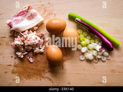 Ham, bacon, eggs, leek on a wooden deck as ingredients for a breakfast - Stock Photo
