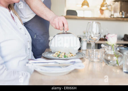 Midsection of waiter lifting cloche for customer in restaurant - Stock Photo