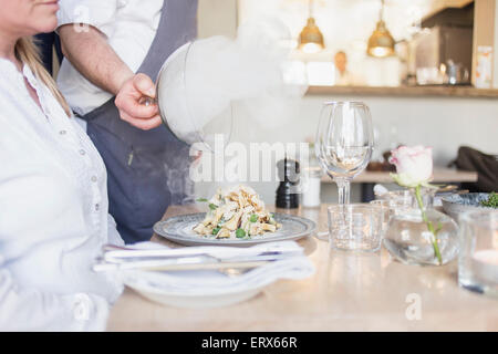 Steam coming out from food while waiter lifting lid in restaurant - Stock Photo