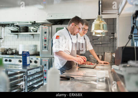 Young chefs with chilies in tray standing together in kitchen - Stock Photo