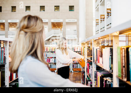 Happy female student choosing book with friend in foreground at library - Stock Photo
