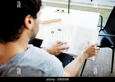Young man reading book at table in library - Stock Photo