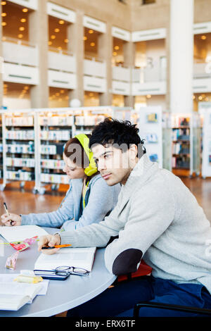 Thoughtful young man looking away while friend reading notes at table in library - Stock Photo
