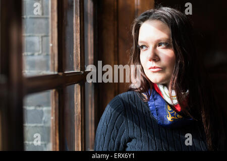 Thoughtful young woman looking through window in cafe - Stock Photo