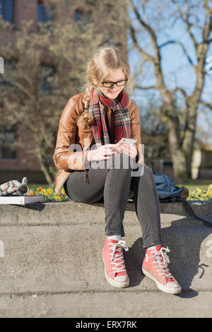 Full length of happy teenage girl using mobile phone while sitting on retaining wall - Stock Photo