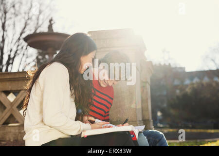 Smiling college students reading book in campus - Stock Photo