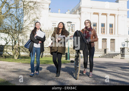 Full length of happy female students walking out of college - Stock Photo