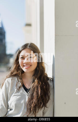 Portrait of smiling teenage girl leaning on wall - Stock Photo