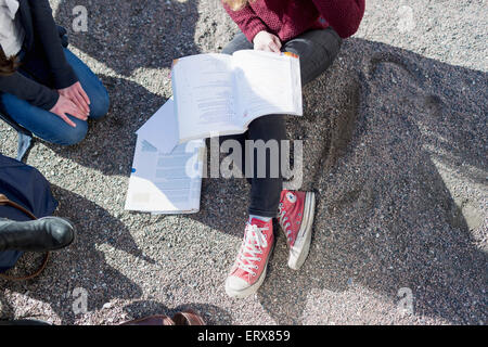 High angle view of teenage girls studying while sitting in college campus - Stock Photo