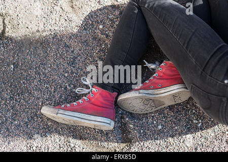 Low section of teenage girl sitting in college campus - Stock Photo