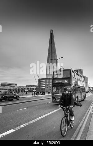 Cyclist crossing London bridge on bike with The Shard in the background, London, UK. - Stock Photo