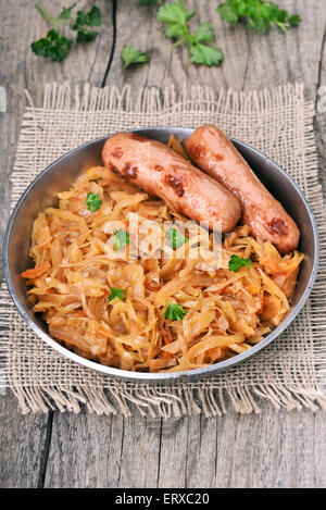 Stew cabbage in pan on wooden background - Stock Photo