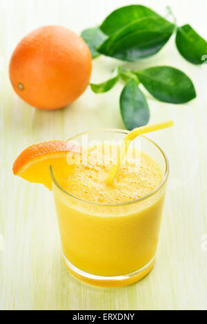 Citrus orange smoothie in glass on green table - Stock Photo