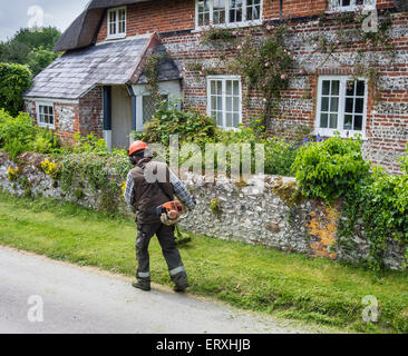 Man using strimmer in the village of Martin, Hampshire, England, UK - Stock Photo