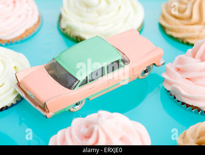 dinky Plymouth Plaza surrounded by cakes in pastel colors. - Stock Photo