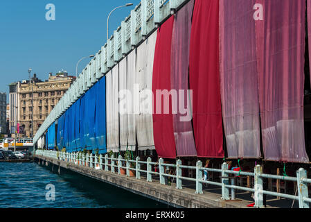 Restaurants on the Galata Bridge in central Istanbul shaded in the heat by colourful awnings - Stock Photo
