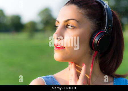 Beautiful Young Woman Listening Music Through Headphones in a Park Close Up - Stock Photo