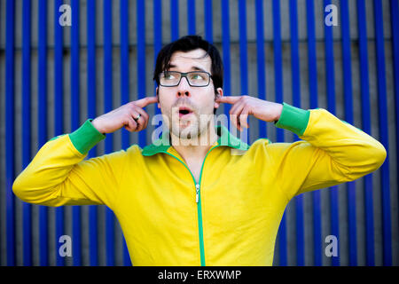 man in yellow trikot shuts his ears with his fingers and pretends not to hear anything - Stock Photo