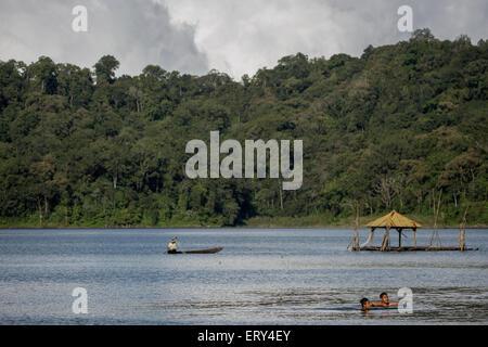 A man rowing a canoe in Lake Buyan, Bali - Stock Photo