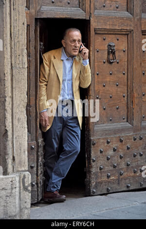 An Italian man speaking on his cellphone in a doorway in Rome, Italy near the Pantheon. - Stock Photo