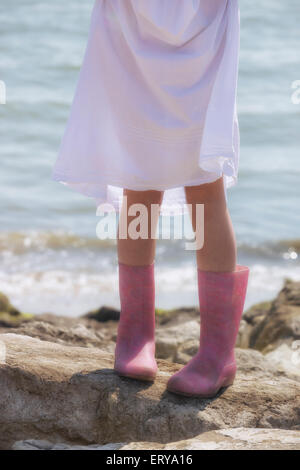 legs of a girl with Wellies on rocks at the sea - Stock Photo