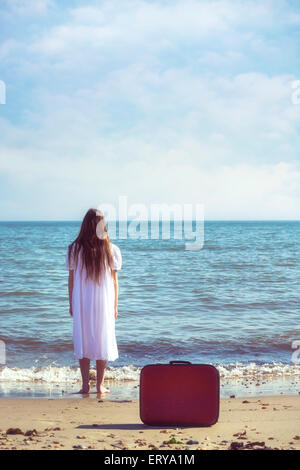 a girl in a white dress is standing on a beach and left a red suitcase behind her - Stock Photo