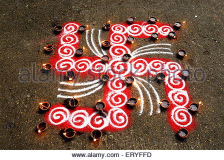 Rangoli floor design with swastik and lighted clay lamps during diwali deepawali festival 2009 - Stock Photo