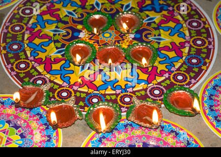 Beautiful colour mat rangoli with oil lamps ; Diwali deepawali festival ; India - Stock Photo