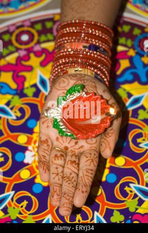 Woman holding diya dip dipak oil lamp ; Mehandi heena pattern with rangoli mat ; Diwali deepawali festival ; India - Stock Photo