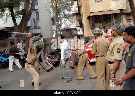 Police charging at man in Bombay ; Mumbai ; Maharashtra ; India NOMR - Stock Photo