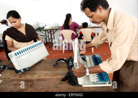 Staff members of Bharat Electronics Limited checking electronic voting machine evm ; Bombay Mumbai ; Maharashtra - Stock Photo
