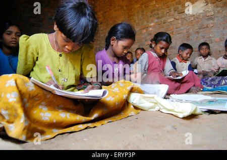 Tribal children girls and boys learning in school run by NGO Non Government Organization in village India - Stock Photo