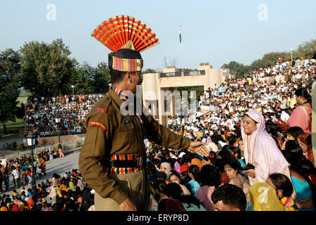 Indian Border Security Force soldier helping audience before retreat ceremony called lowering flags - Stock Photo