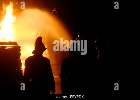 Fire brigade personnel cool fire broke out in LPG tanker with water shots at Kurla ; Bombay Mumbai ; Maharashtra - Stock Photo