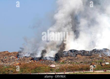 Burning garbage in dumping ground ; Deonar ; Bombay Mumbai ; Maharashtra ; India - Stock Photo