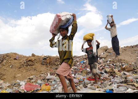 Rag pickers carrying load in dumping ground Deonar Bombay Mumbai Maharashtra India - Stock Photo