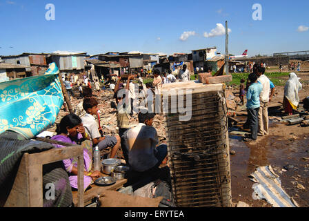 Slum dwellers sitting with their belongings after demolition of slums on Sahar airport Chatrapati Shivaji International - Stock Photo
