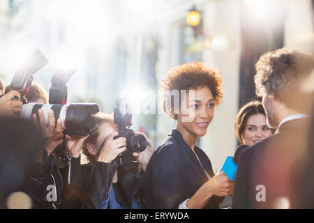 Celebrity being interviewed and photographed by paparazzi at event - Stock Photo